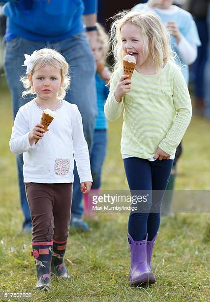 Isla Phillips and Savannah Phillips and eat ice creams as they attend the Gatcombe Horse Trails at Gatcombe Park Minchinhampton on March 25 2016 in...