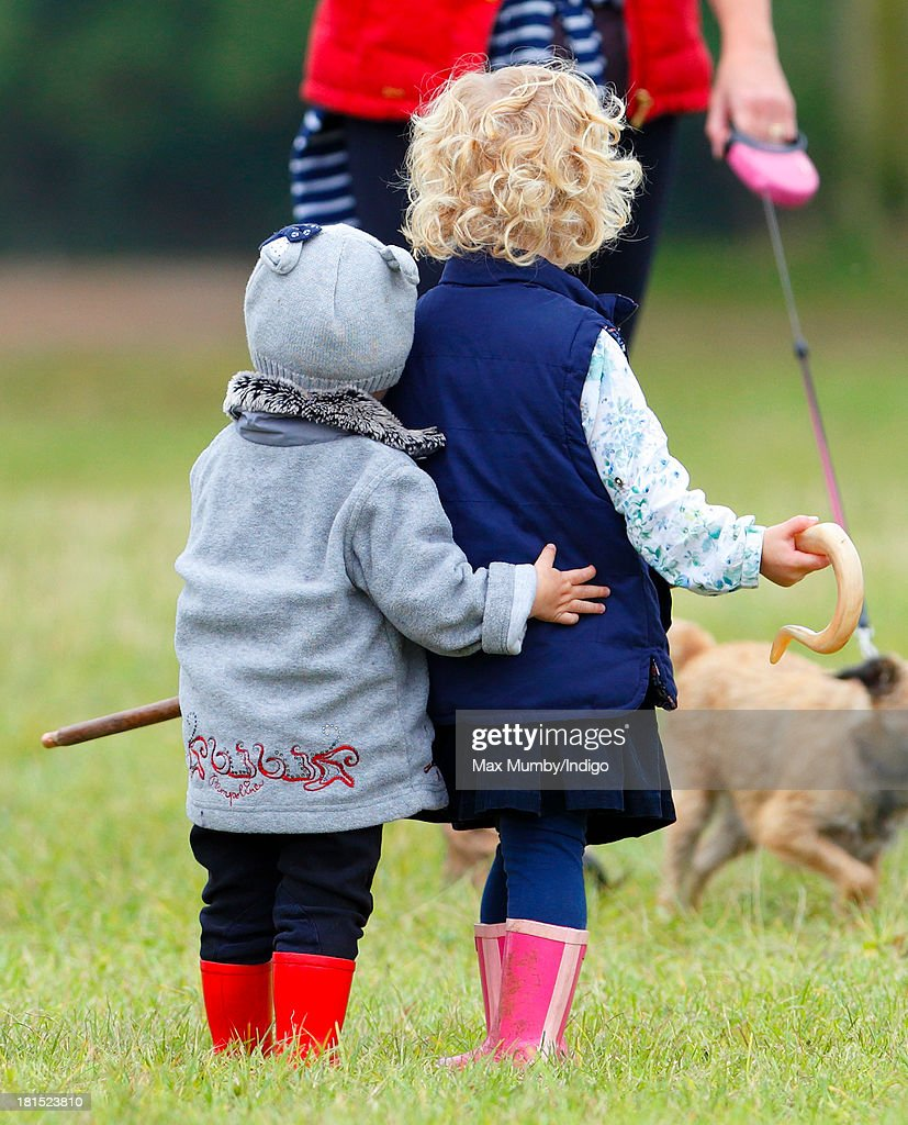 Isla Phillips (left) and Savannah Phillips (right) play with their Grandmother's (Princess Anne, The Princess Royal) shepherds crook as they and their parents Peter and Autumn Phillips attend the Gatcombe Horse Trials at Gatcombe Park, Minchinhampton on September 21, 2013 in Stroud, England.