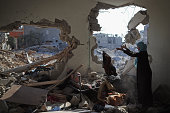 Islam El Masri begins to sort through the rubble of her destroyed home on August 14 2014 in Beit Hanoun Gaza A new fiveday ceasefire between...