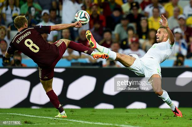 Islam Slimani of Algeria and Denis Glushakov of Russia compete for the ball during the 2014 FIFA World Cup Brazil Group H match between Algeria and...