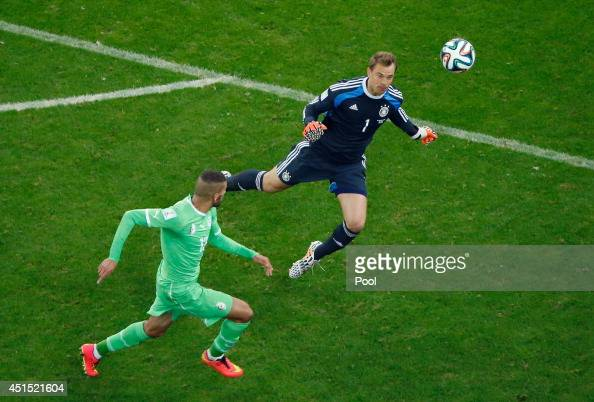 Islam Slimani of Algeria attempts a shot at goal against goalkeeper Manuel Neuer of Germany during the 2014 FIFA World Cup Brazil Round of 16 match...