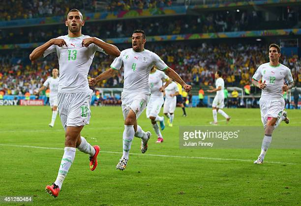 Islam Slimani of Algeria celebrates scoring his team's first goal with teammates Essaid Belkalem and Carl Medjani during the 2014 FIFA World Cup...