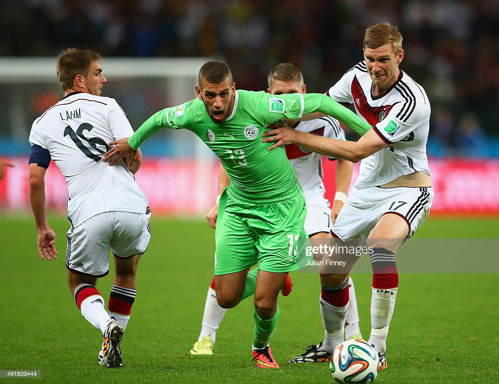 <a gi-track='captionPersonalityLinkClicked' href=/galleries/search?phrase=Islam+Slimani&family=editorial&specificpeople=9704639 ng-click='$event.stopPropagation()'>Islam Slimani</a> of Algeria is challenged by <a gi-track='captionPersonalityLinkClicked' href=/galleries/search?phrase=Philipp+Lahm&family=editorial&specificpeople=483746 ng-click='$event.stopPropagation()'>Philipp Lahm</a> (L) and <a gi-track='captionPersonalityLinkClicked' href=/galleries/search?phrase=Per+Mertesacker&family=editorial&specificpeople=207135 ng-click='$event.stopPropagation()'>Per Mertesacker</a> of Germany during the 2014 FIFA World Cup Brazil Round of 16 match between Germany and Algeria at Estadio Beira-Rio on June 30, 2014 in Porto Alegre, Brazil.