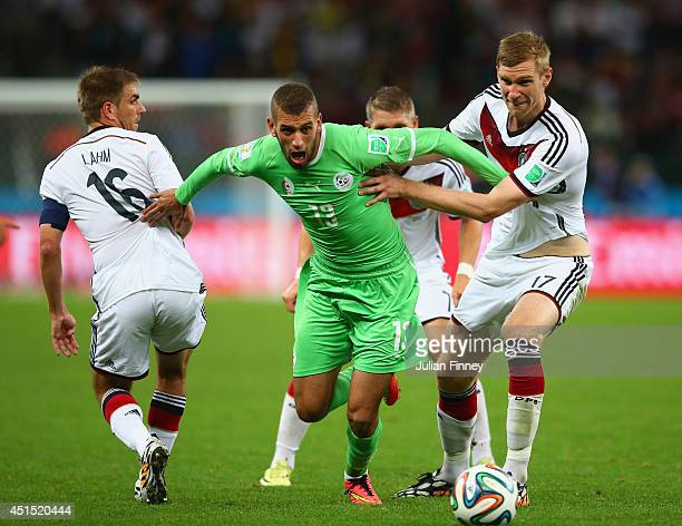 Islam Slimani of Algeria is challenged by Philipp Lahm and Per Mertesacker of Germany during the 2014 FIFA World Cup Brazil Round of 16 match between...