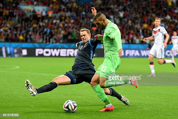 Islam Slimani of Algeria tries to shoot at goal while Manuel Neuer of Germany tackles to block outside the penalty area during the 2014 FIFA World...