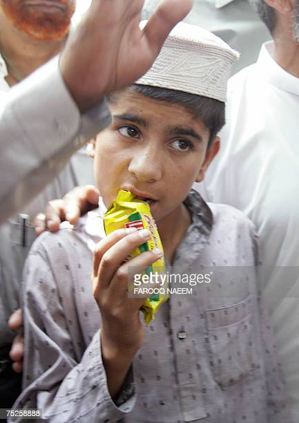 A Pakistani child who escaped from the beseiged Red Mosque opens a pack of biscuits as he is escorted by army soldiers in Islamabad 07 July 2007...