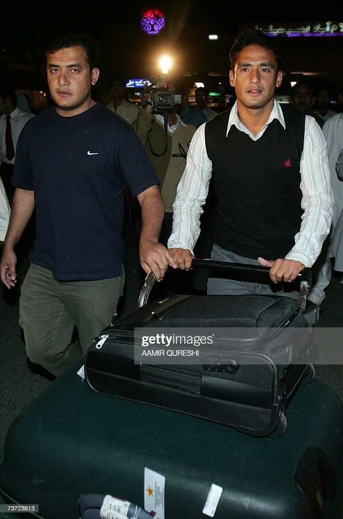 Pakistani cricketer Yasir Arafat (R) walks with his brother (L) upon his arrival to Islamabad airport, 28 March 2007, after a two-day stopover in London. Pakistan's cricket chief promised legislators that players will get legal aid if they are summoned to Jamaica for questioning over the murder of Coach Bob Woolmer. Pakistan Cricket Board chairman Naseem Ashraf was also asked when he appeared before the senate committee for sports about the team's poor performance at the World Cup, where Pakistan were dumped out by Ireland. AFP PHOTO/Aamir QURESHI