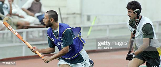 Pakistani field hockey player Shakeel Abbasi juggles a ball as he teammate Dilawar Hussain looks on during a practice session in Islamabad 13 October...