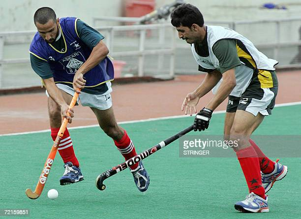 Pakistani field hockey player Shakeel Abbasi fights for the ball with his teammate Dilawar Hussain during a practice session in Islamabad 13 October...