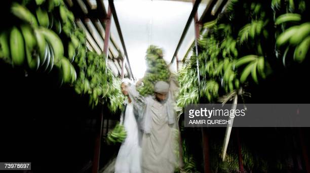Pakistani labourers carry bunches of bananas at a fruit and vegetable market on the outskirts of Islamabad 26 April 2007 Pakistan's economy is...