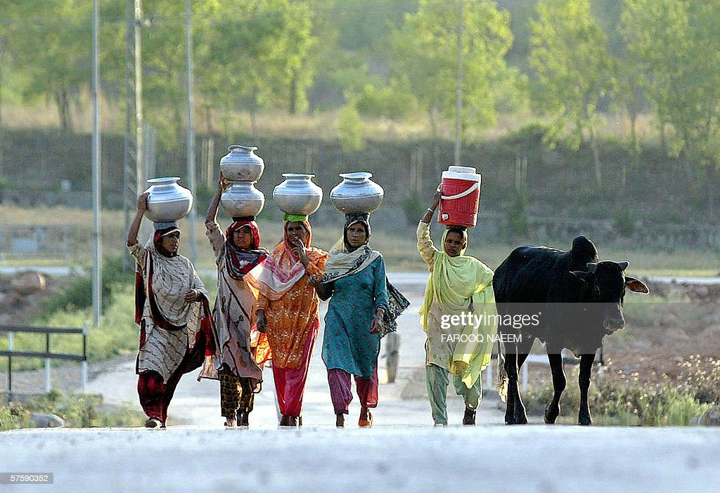 Pakistani women carry water in pitchers in Islamabad, 12 May 2006, as heat waves caused severe water shortage in some areas. A scorching heatwave in central Pakistan has killed at least 51 people in the past week, with temperatures rising as high as 50 degrees Celsius (122 Fahrenheit), officials said. AFP PHOTO/Farooq NAEEM