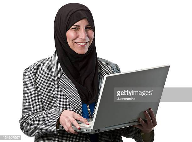 Islamic business woman with head scarf holding laptop.