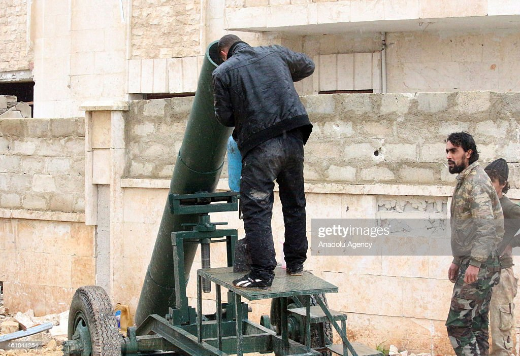 Islamic Front members load the rockets to launcher as they clash with the Assad regime forces in the Majbal region of Aleppo, Syria on January 5, 2015.