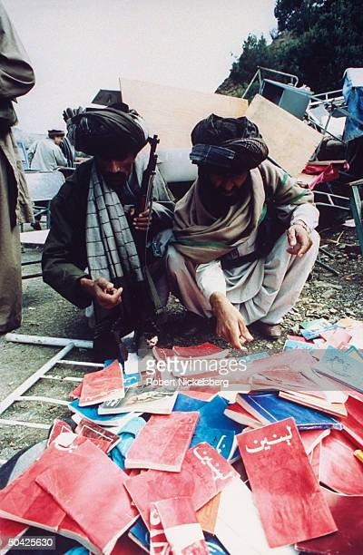 Islamic Mujahedeen crouching examining pile of captured communist LENINentitled booklets taken fr Khost heavily fortified garrison seized in 16day...