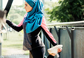 Islamic woman stretching after workout at the park