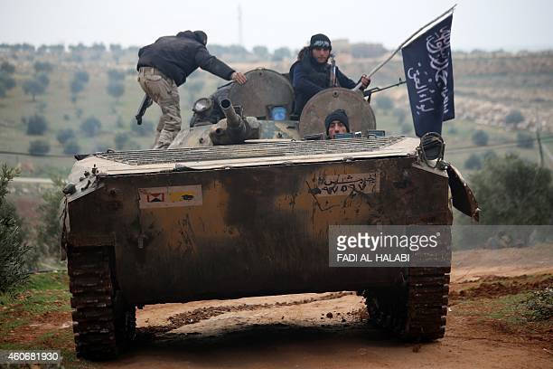 Islamist fighters from the Liwa alHaq brigade drive a tank they seized from Syrian forces loyal to the regime as they fight against them on December...