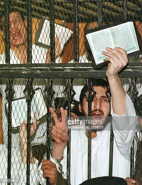 Islamist militants of the group Jamaa Islamiyya brandish the holy Koran behind the bars of their jail 27 January in Cairo Egypt's state security high...