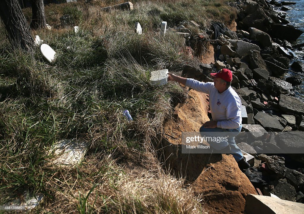 Island resident Donny Willey picks up a grave marker from a grave that was once several yards from the waters edge are now exposed and releasing...