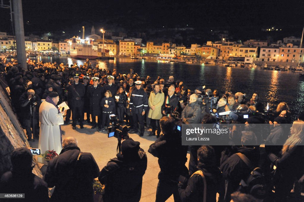 Island residents take part in a candlelight vigil before holding a minute of silence to mark the exact time that the Costa Concordia ship crashed on...