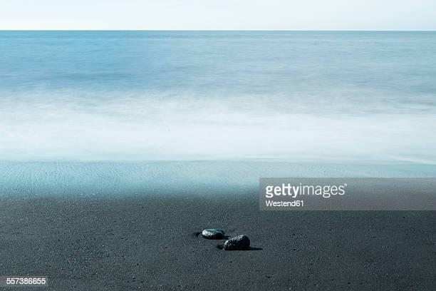 Island, two pebbles lying on dark sandy beach at waterfront