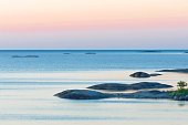 Islets in the archipelago during the sunrise. Red and blue shades