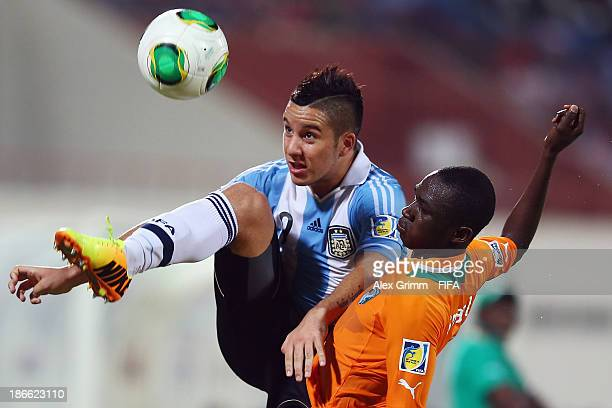 Ismael Diallo of Ivory Coast is challenged by Sebastian Driussi of Argentina during the FIFA U17 World Cup UAE 2013 Quarter Final match between...