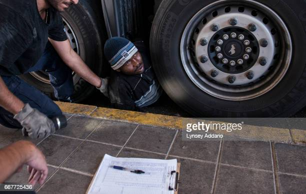 Ismael from Zallingi Darfur is pulled out from underneath a truck by Greek border security during a search for illegal migrants trying to sneak from...