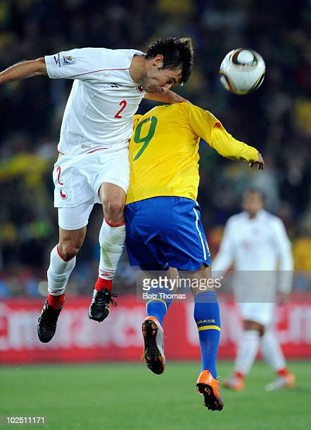 Ismael Fuentes of Chile heads the ball while challenged by Luis Fabiano of Brazil during the 2010 FIFA World Cup South Africa Round of Sixteen match...