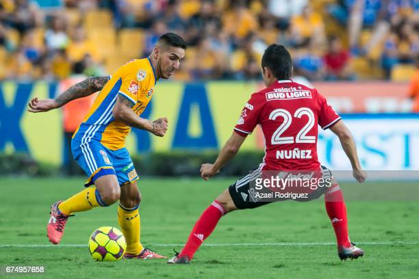 Ismael Sosa of Tigres defends the ball from Juan Nunez of Tijuana during the 16th round match between Tigres UANL and Tijuana as part of the Torneo...