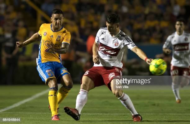 Ismael Sosa of Tigres fights for the ball with Guido Rodriguez of Tijuana during the semi finals first leg match between Tigres UANL and Tijuana as...