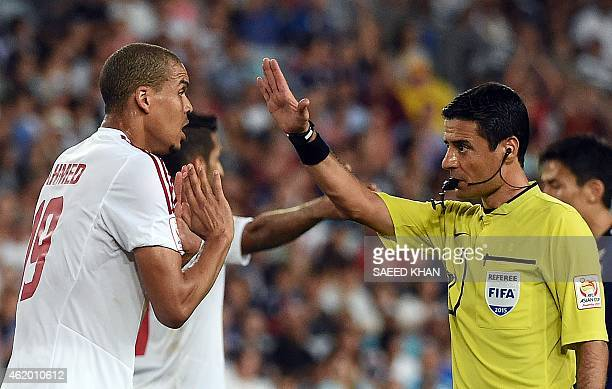 Ismail Ahmed of the United Arab Emirates talks with match referee Alireza Faghani of Iran during the quarterfinal football match between Japan and...