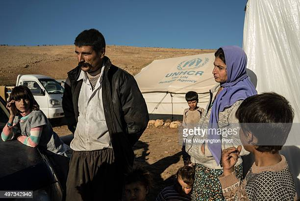 Ismail Mirza stands with his family outside a tent where they live after fleeing Sinjar when ISIS attacked the city in August last year
