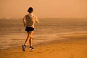 isolated background back portrait of young happy and attractive fit woman running on the beach in outdoors jogging workout in fitness training and healthy sporty lifestyle concept