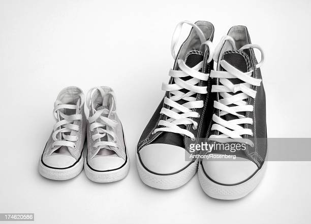 Isolated black and white images of adult and child sneakers