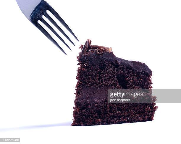 isolated cake being eaten with  fork