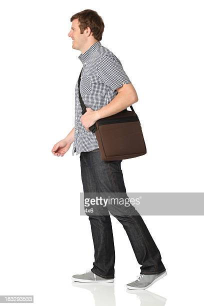 Isolated casual man walking with shoulder bag