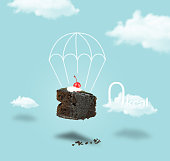 Isolated Chocolate cherry cake with parachute on blue sky background. Chocolate pie. Flying brownie with cream.