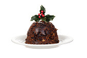 isolated christmas brandy pudding on plate with holly on white background