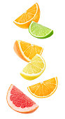 Isolated citrus fruits wedges. Falling pieces of orange, lemon, lime and grapefruit isolated on white background with clipping path