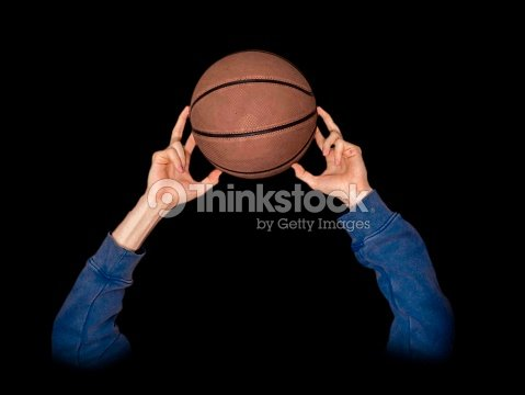 isolated hand holding basketball close up on black background stock