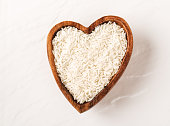 Isolated handful of raw rice in the wood bowl on white background