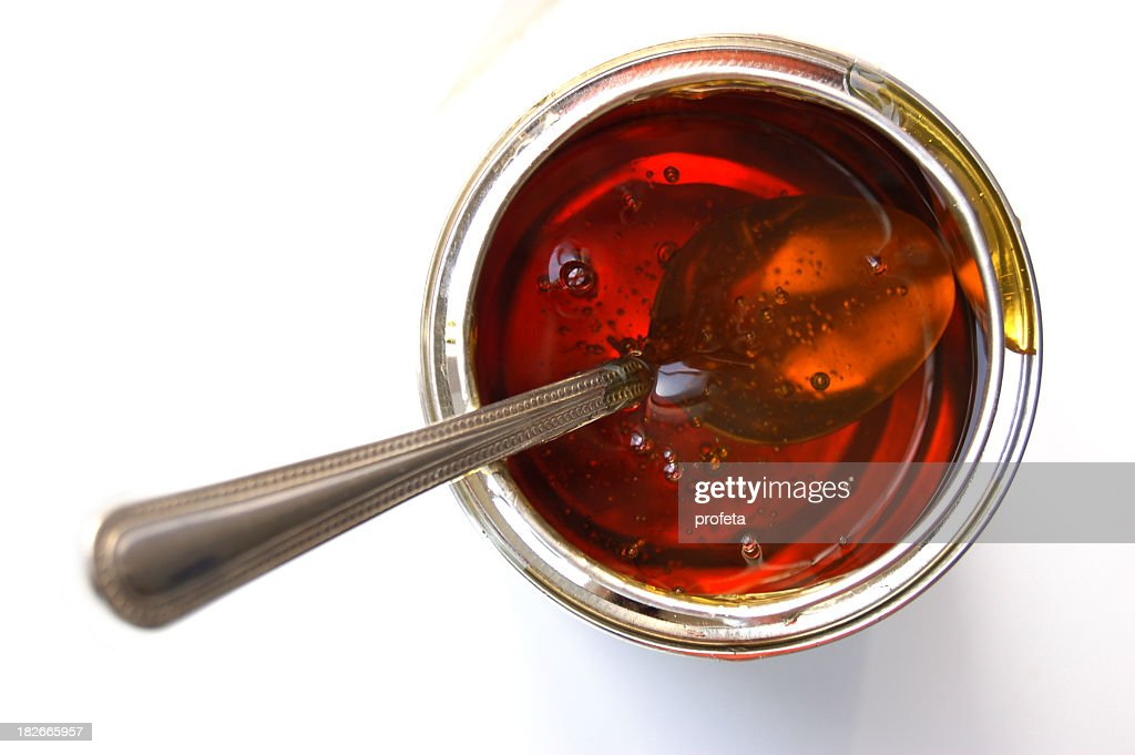 Isolated image of a spoon inside a jar of syrup