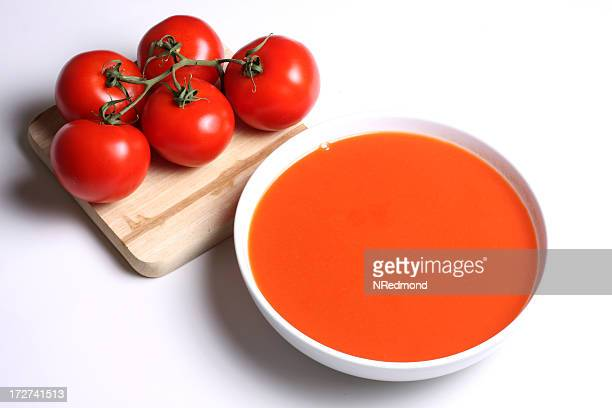 Isolated image of tomato soup next to a couple of tomatoes