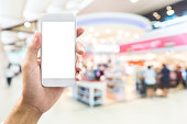isolated man hand holding smart phone over abstract blurred background with bokeh in shopping mall, department store