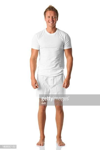 Isolé homme debout dans une chemise blanche et un boxer