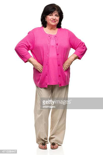 Isolated middle aged woman in a pink shirt and tan pants
