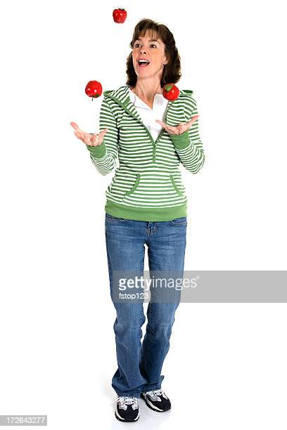 Isolated on White:  woman juggling apples.