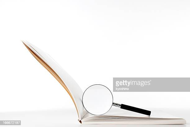 Isolated shot of blank book with magnifying glass on white