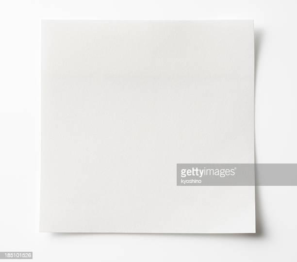 Feuillet autoadhésif vide blanc sur un fond blanc.