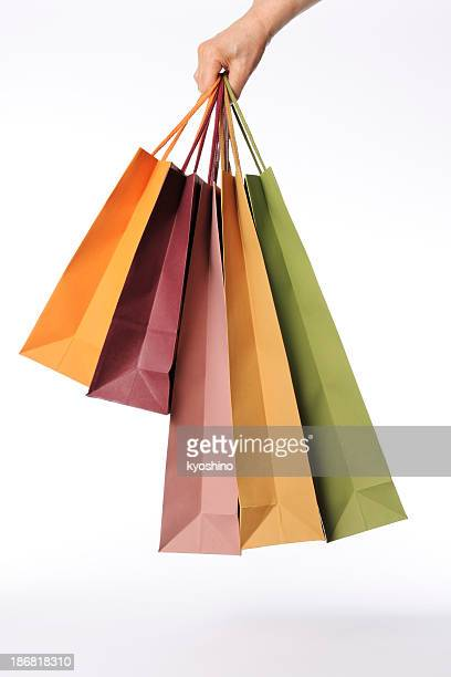 Isolated shot of hand carrying shopping bags against white background